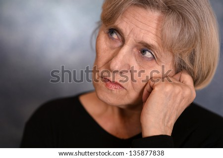 close-up portrait of an elderly woman  on a gray background
