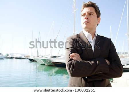 Close up portrait of an elegant businessman standing by a luxury yachts marine with his arms crossed against a blue sky, being thoughtful.
