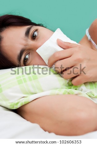 Close-up portrait of an hispanic woman sick with the flu laying in bed and holding a white paper tissue
