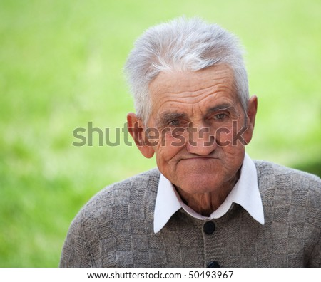 Close up portrait of an old farmer over blurred green background