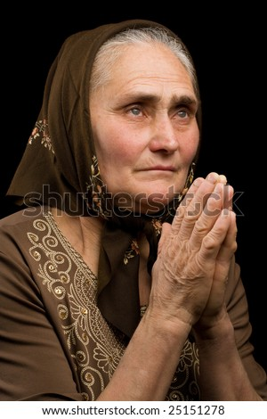 Close up portrait of an old woman praying