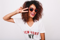 Close-up portrait of attractive black female model with red manicure isolated on white background. Photo of happy african girl in sunglasses posing with peace sign in studio.