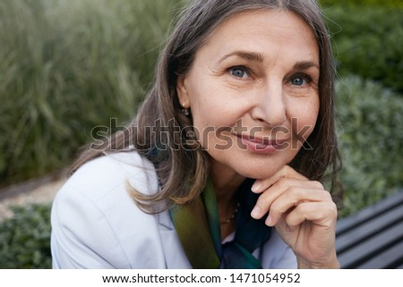 Close up portrait of attractive charming senior mature female with gray hair, blue eyes and wrinkled skin keeping hand on her chin, looking at camera with joyful smile. Maturity and aging concept