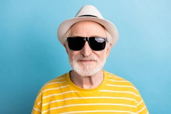 Close-up portrait of attractive cool man wearing black sun specs isolated over bright blue color background