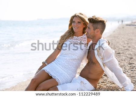 Close up portrait of Attractive couple in white sitting on pebble beach.