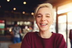 Close up portrait of attractive female international student having fun during break in coffee shop waiting for classmates meeting sitting near copy space area for your advertising messages or content