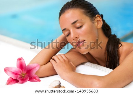 Close up portrait of attractive girl relaxing in spa pool.