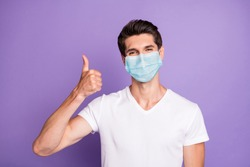 Close-up portrait of attractive healthy guy wearing safety gauze mask showing thumbup influenza preventive measures isolated bright vivid shine vibrant lilac violet purple color background
