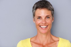 Close up portrait of attractive middle age woman smiling against gray background