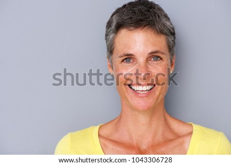 Close up portrait of attractive middle age woman smiling against gray background #1043306728