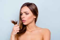 Close up portrait of attractive pretty brown haired she her girl displeased with hair ends need to do haircut cut off bad ends dyeing not dressed isolated on grey background