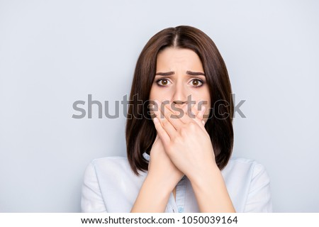 Close up portrait of attractive, pretty, cute,  stylish charming, woman in shirt closed her mouth with crossed palms with worried expression, she can't say anything, standing over grey background
