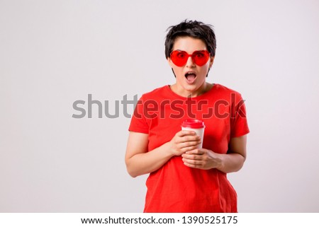 Close-up portrait of attractive pretty cute stylish cute cute cute funny brunette in everyday red t-shirt holding looking at paper Cup of coffee isolated on white background,concept of love for coffe #1390525175