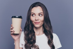 Close-up portrait of attractive pretty lovely stylish nice cute cheerful curly-haired brunette girl in casual white t-shirt, holding, looking at paper-cup coffee, isolated on grey background