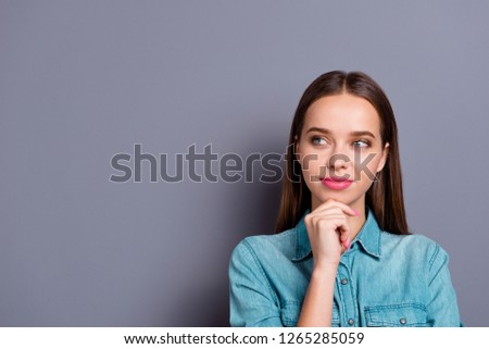 Close up portrait of attractive thinking with interest touching chin young woman wearing casual denim jeans shirt isolated on grey background