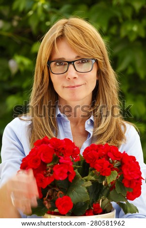 Close-up portrait of attractive woman standing at garden at home while looking at camera and holding potted flower in her hands.