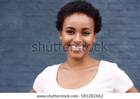 Close up portrait of attractive young black woman smiling - Shutterstock ID 581282662