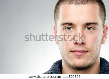 Close-up portrait of attractive young man on gray background with copy space