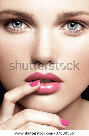 close-up portrait of attractive young model with bright make-up and manicure