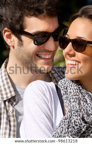 Close up portrait of attractive young smiling couple with sunglasses outdoors.