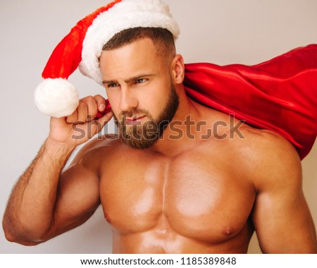 Close up portrait of bearded handsome man with christmas hat and bag