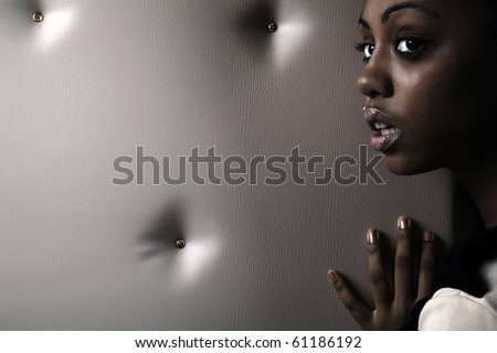 Close-up portrait of Beautiful African woman pose on a beige leather background.
