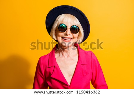 Close up portrait of beautiful and happy blond hair grandma looking at camera isolated on yellow background