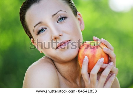 Close-up portrait of beautiful brunette woman holding red apple at summer green park.