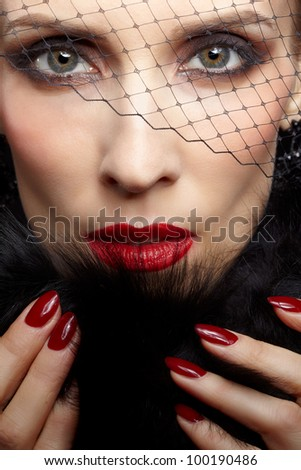 close-up portrait of beautiful brunette woman in veil touching black fur coat with manicured fingers