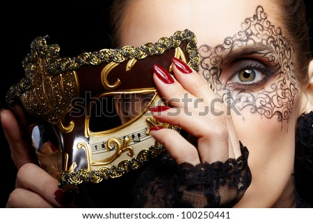 close-up portrait of beautiful brunette woman with facial body art hiding half of her face with carnival venetian mask