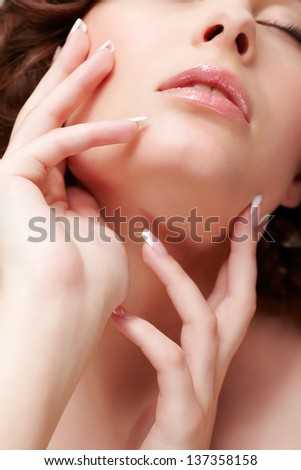 close-up portrait of beautiful brunette young woman with french manicure closing eyes