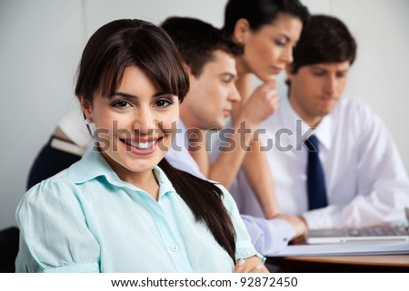 Close-up portrait of beautiful businesswoman smiling while team working in background