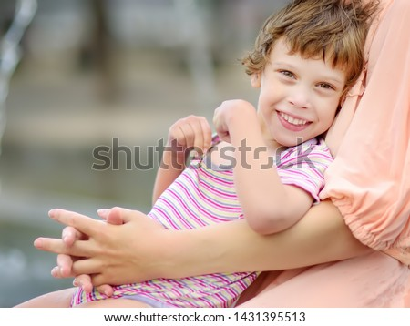 Close-up portrait of beautiful disabled girl in the arms of his mother having fun in fountain of public park at sunny summer day. Child cerebral palsy. Inclusion. Stock photo ©