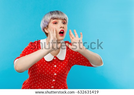 Close up portrait of beautiful dollish girl with short light violet hair wearing red dress shouting over blue background. Stock photo ©