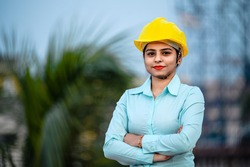 Close up portrait of beautiful female engineer wearing a protective helmet and looking at camera.