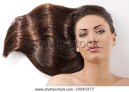 close-up portrait of beautiful female face with long dark waved hairs laying down on the floor
