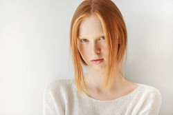 Close up portrait of beautiful freckled Caucasian teenage girl with red hair and blue eyes looking and smiling at the camera. Student girl posing against white copy space studio wall background