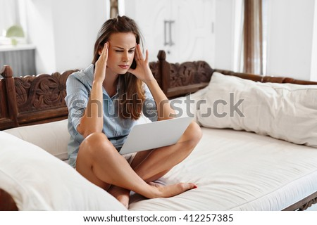 Close Up Portrait Of Beautiful Frustrated Or Stressed Woman Having Headache While Working On Laptop Computer At Home. Girl Feeling Head Pain, She Is Exhausted And Tired. Work Stress, Health Concept