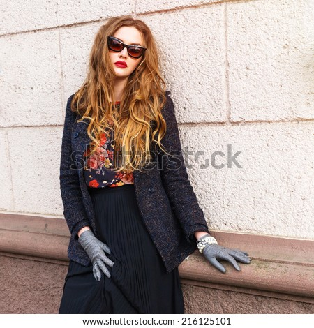 Close up portrait of beautiful ginger woman with perfect long fluffy hairs, wearing stylish elegant clothes. Autumn retro style. Pink urban background.