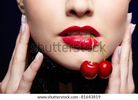 close-up portrait of beautiful girl's lower part of face with two red cherries in mouth