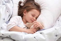 Close up portrait of beautiful girl sleeping in pajama in bed with her teddy bear, lying on pillow with closed eyes, charming cute female kid having dark hair. Childhood and morning time concept.