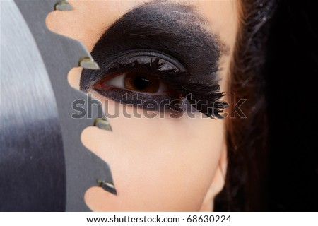 close-up portrait of beautiful girl with bird of prey fantasy make-up with circular saw blade