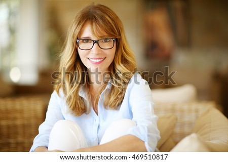Close-up portrait of beautiful happy woman looking at camera and smiling while sitting on sofa.