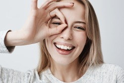 Close up portrait of beautiful joyful blonde Caucasian female smiling, demonstrating white teeth, looking at the camera through fingers in okay gesture. Face expressions, emotions, and body language