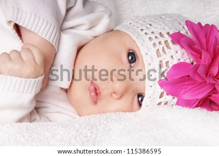 Close-up portrait of beautiful newborn baby girl in knitting hat with bright pink flower, studio shot