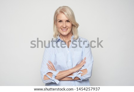 Close up portrait of beautiful old adult caucasian blonde glad cheerful lady smiling, isolated over grey background