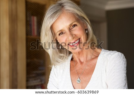 Close up portrait of beautiful older woman standing in study smiling