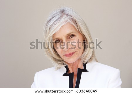 Close up portrait of beautiful older woman staring standing by wall
