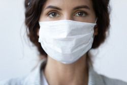 Close up portrait of beautiful 30s young millennial woman cover her face wearing facial medical blue mask, anti-coronavirus COVID-19 pandemic infectious disease outbreak protection, healthcare concept
