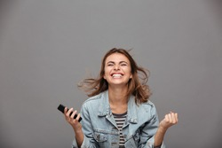 Close-up portrait of beautiful screaming young girl holding smartphone showing winner gesture, isolated on gray background